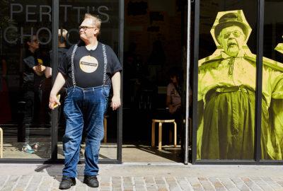 Sami Helle Pertti's Choice Pop Up -kaupan edustalla Lontoossa. Kalevi Helvetin kuva on kiinnitetty lasiseen oveen Sami Helteen takana.