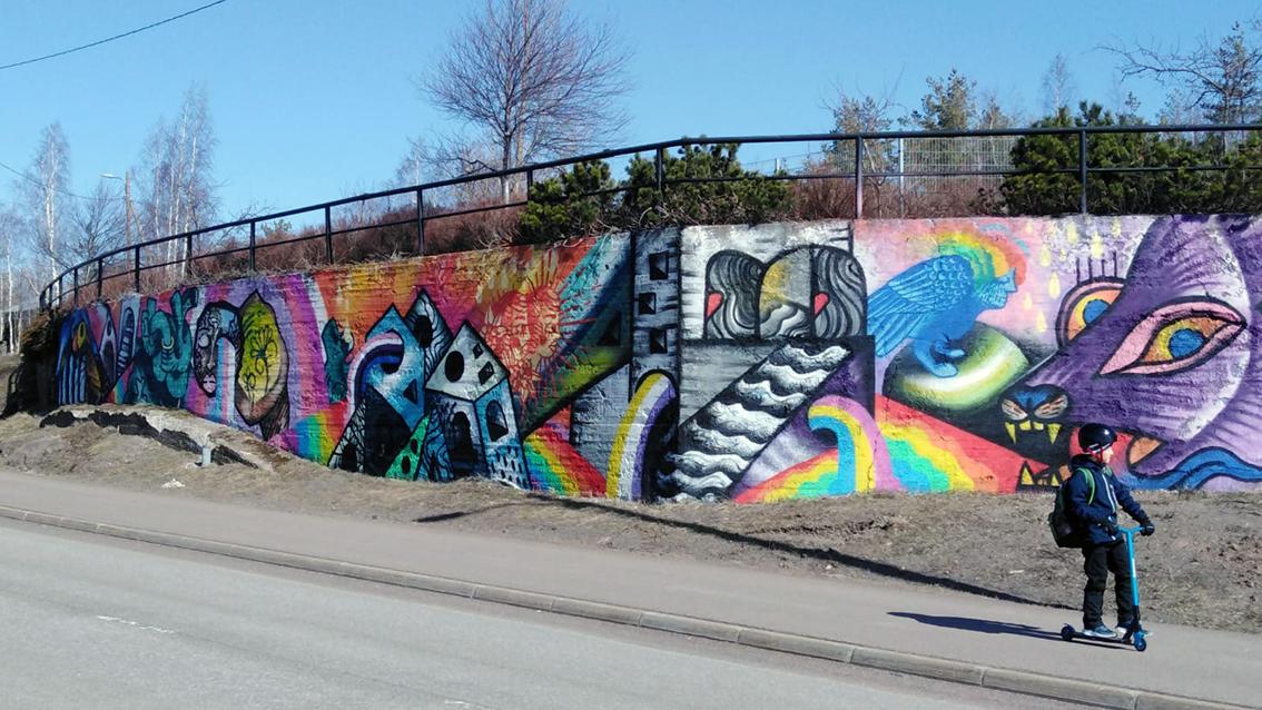 Värikäs graffitiseinä betonimuurissa tien vieressä. Etualalla lapsi potkulautailee.