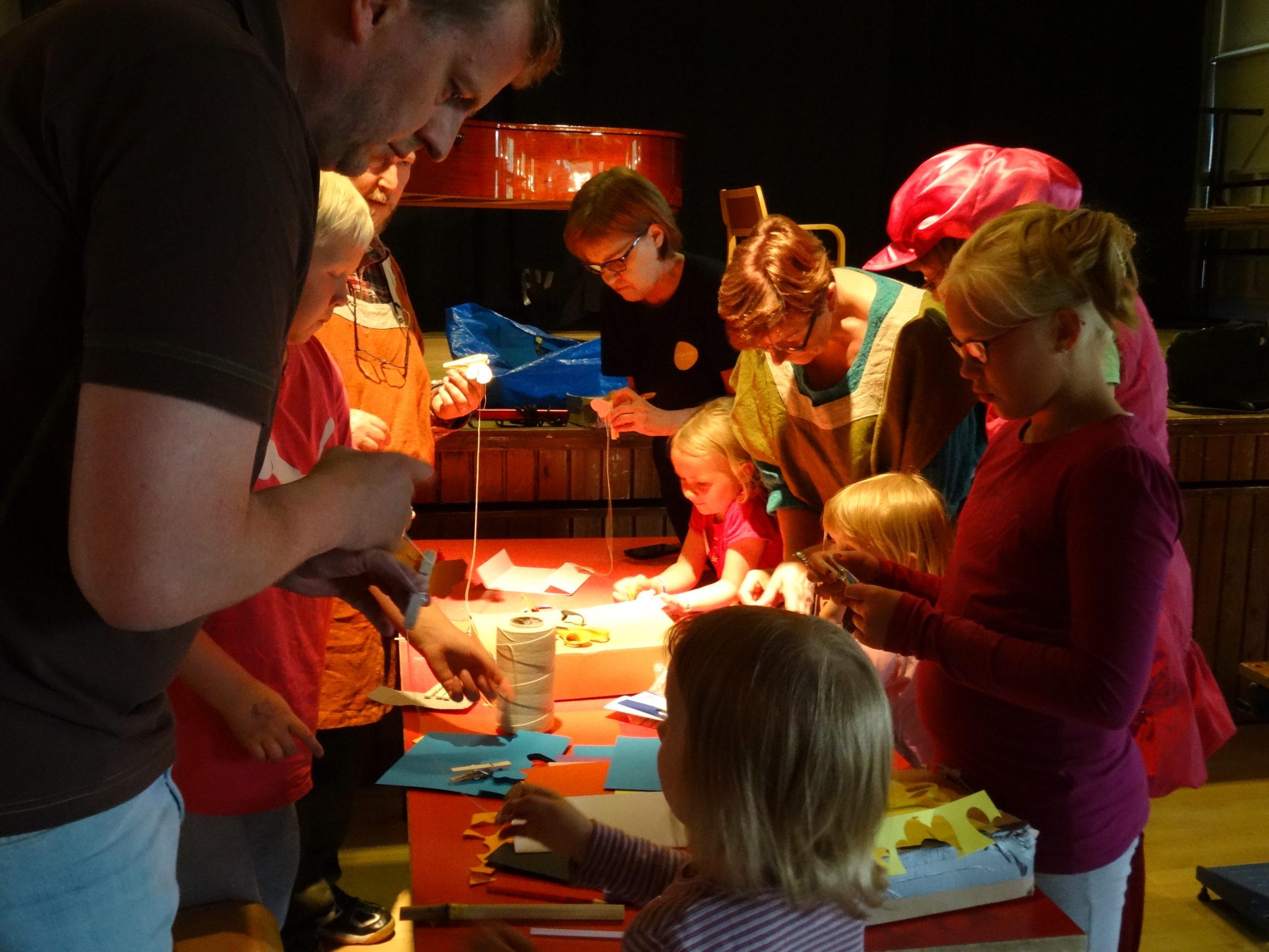 Taidetyöpaja, jossa on lapsia ja aikuisia pyödän äärellä askartelemassa eri materiaaleista taideteoksia.