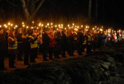 Pimeä talvinen, lumeton ilta. Paljon ihmisiä ulkona käsissään soihdut.