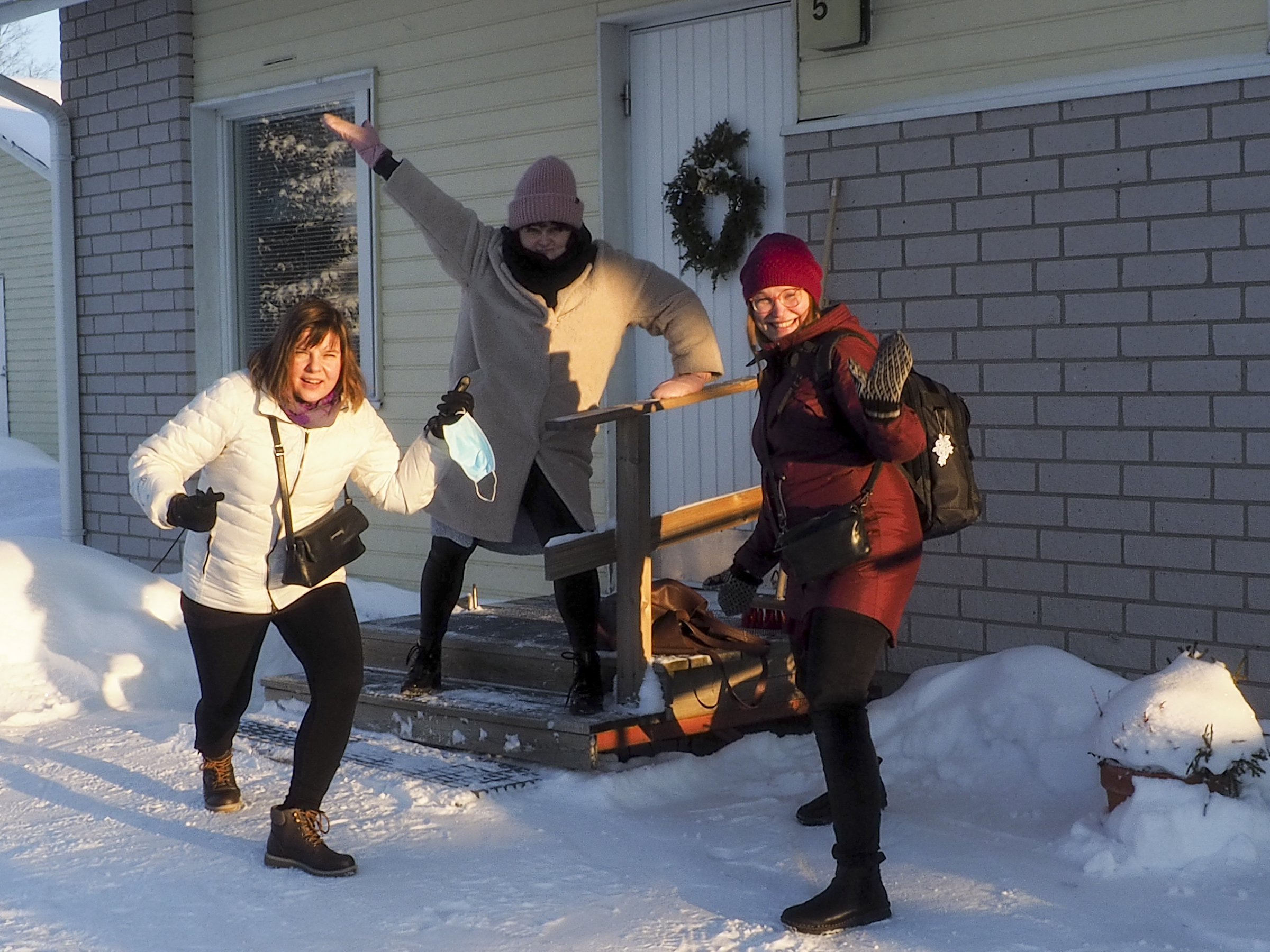 Kolme henkilöä talon edustalla. Talvi.
