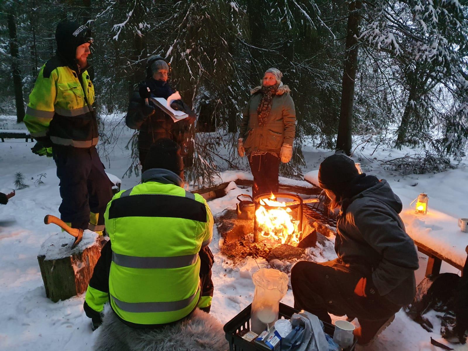 Viisi henkilöä ulkona nuotion äärellä talvisessa metsässä.