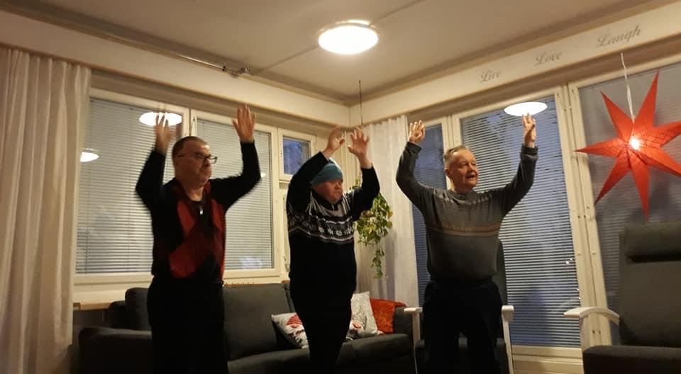 Kolme henkilöä liikkumassa kädet ylhäällä sisällä olohuoneessa.