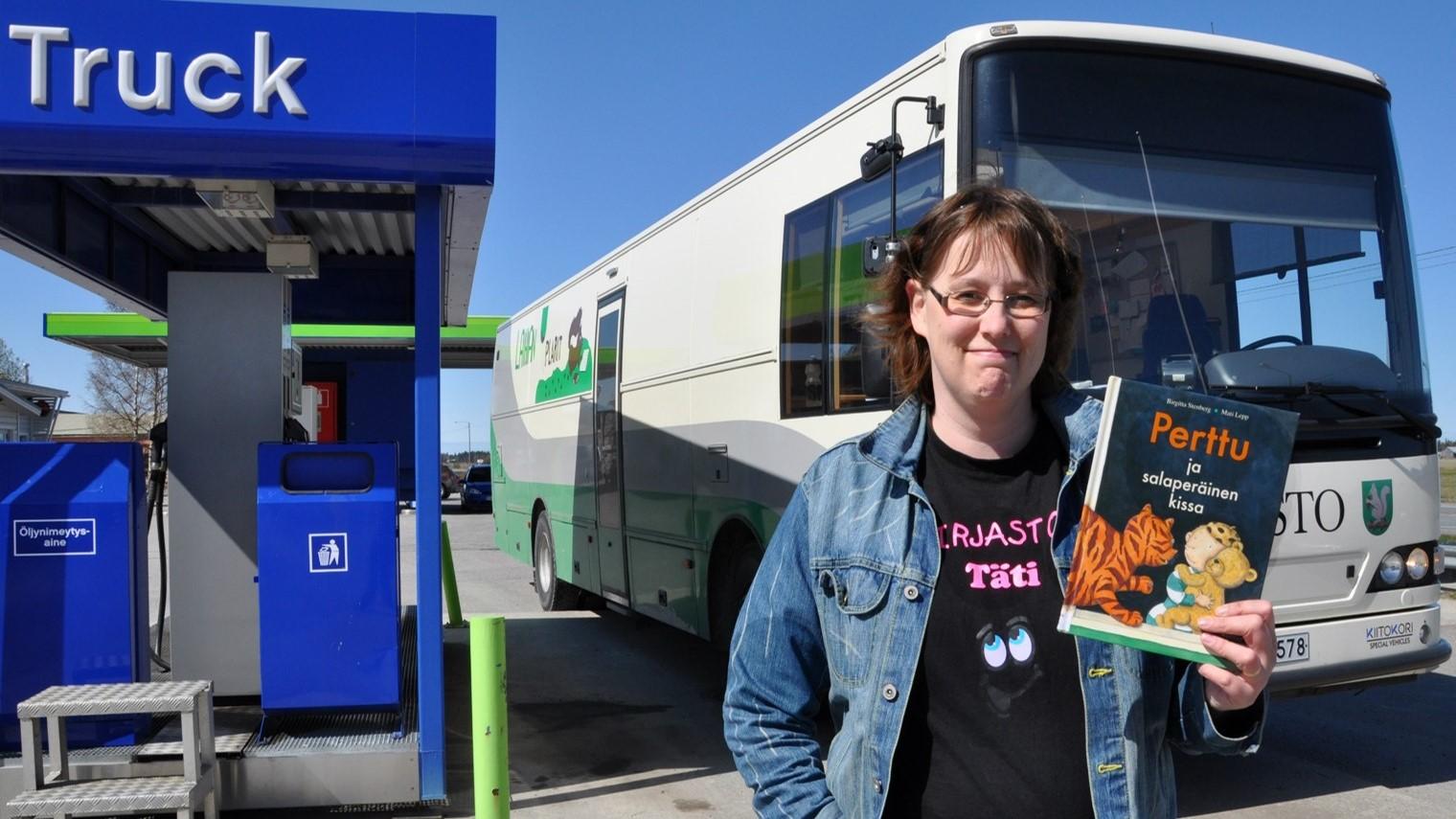 Kirjastoauto tankkausasemalla. Auton edessä on nainen kirja kädessään. Naisen paidassa lukee kirastotäti. Kädessä olevan kirjan nimi on Perttu ja salaperäinen kissa. Se on lastenkirja.