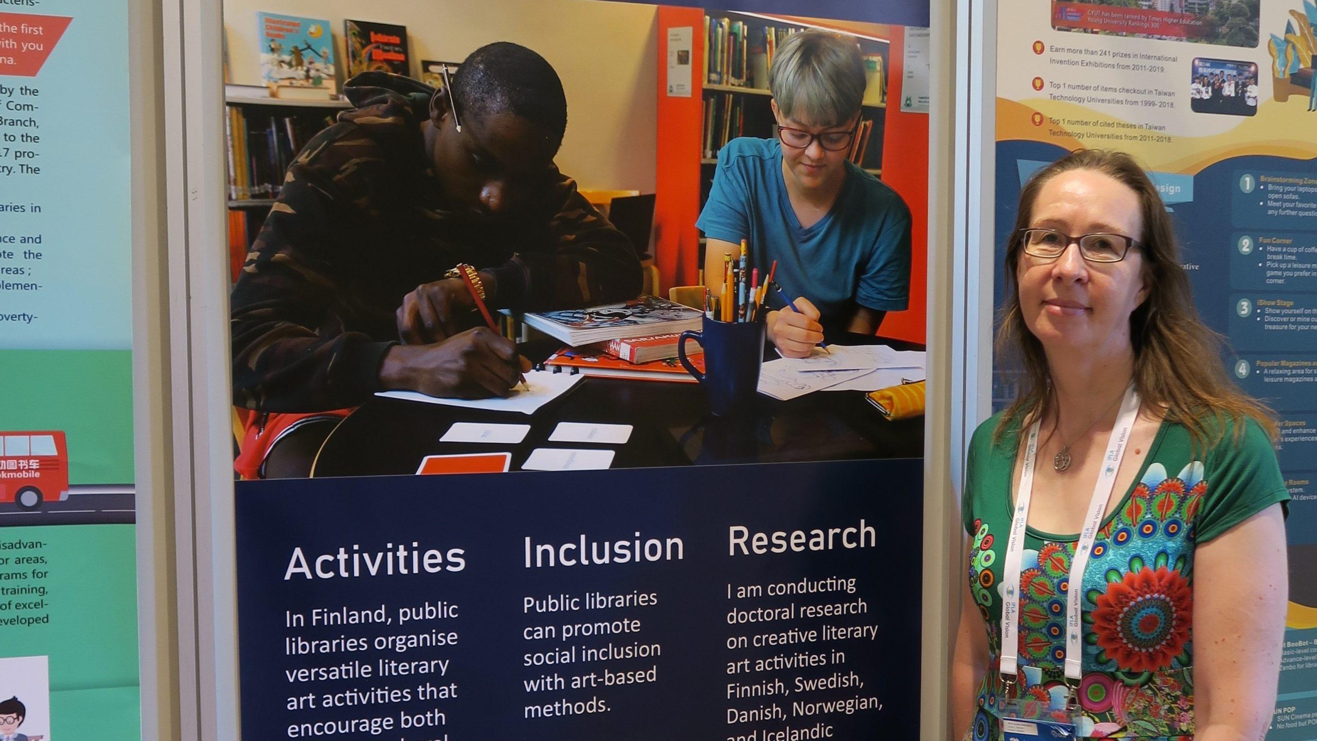 Hanna Kleemola seisoo englanninkielisen posteri-esittelyn vieressä. Posterista on erotettavissa selkeästi sanat Activity, Inclusion ja Research. Posterissa olevassa kuvassa on kuvattu kaksi nuorta kirjastossa pöydän ääressä kirjoittamassa.