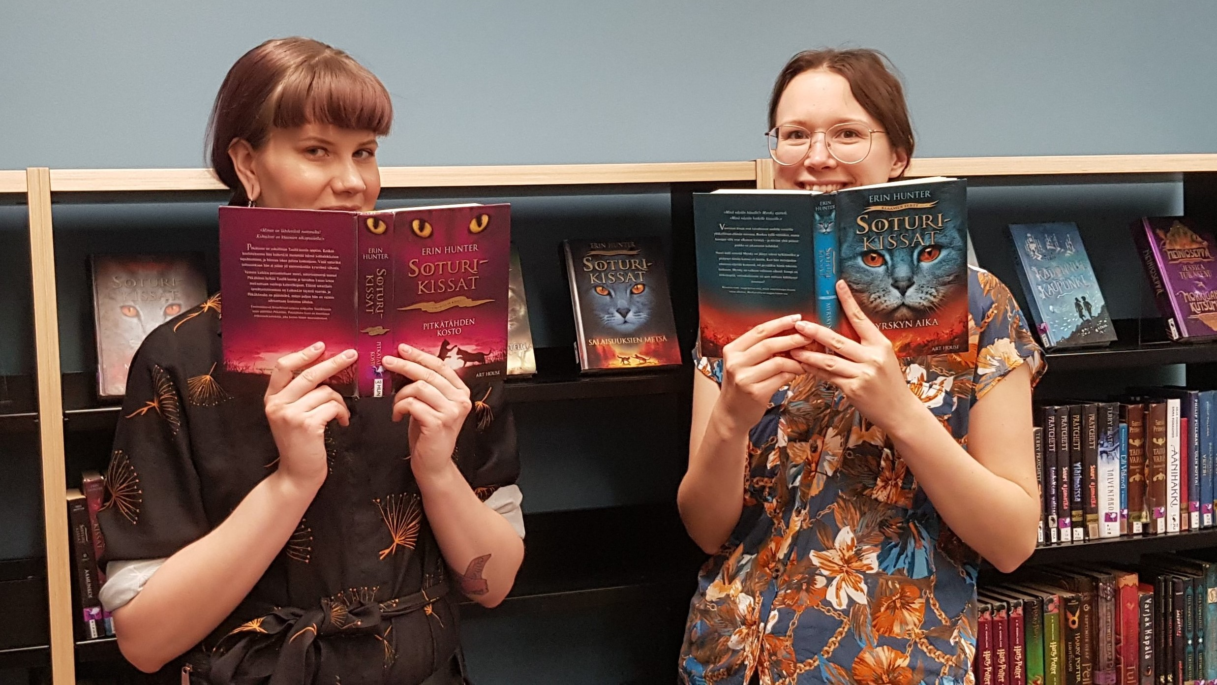 Kaksi nuorta naista seisoo kirjahyllyn edessä. Molemmilla on käsissään Soturikissat-kirjasarjan osa. Kirja peittää naisten kasvojen alaosan.