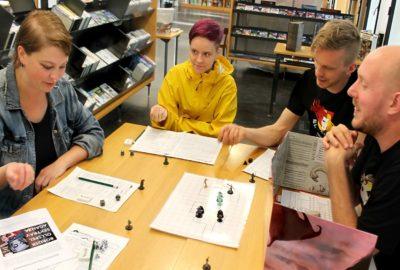 Neljä ihmistä pelaa pöydän äärellä lautapeliä kirjastossa.