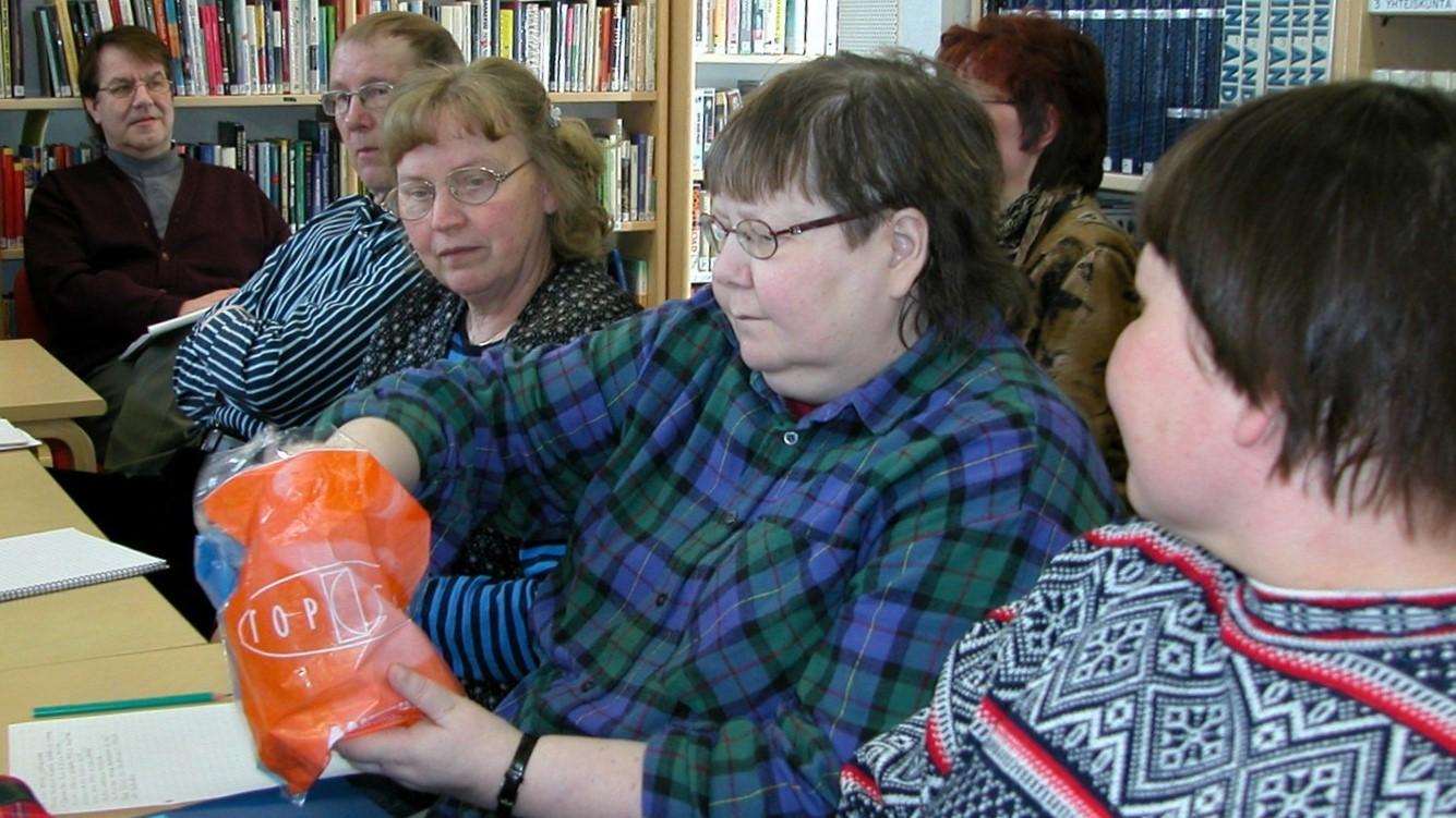 Kuusi hieman vanhempaa ihmistä kirjastossa istumassa pöydän äärellä, ehkä osallistumassa sanataidetyöpajaan. Yksi osallistujista ottaa kädessään olevasta muovipussista jotakin ja muut katsovat.