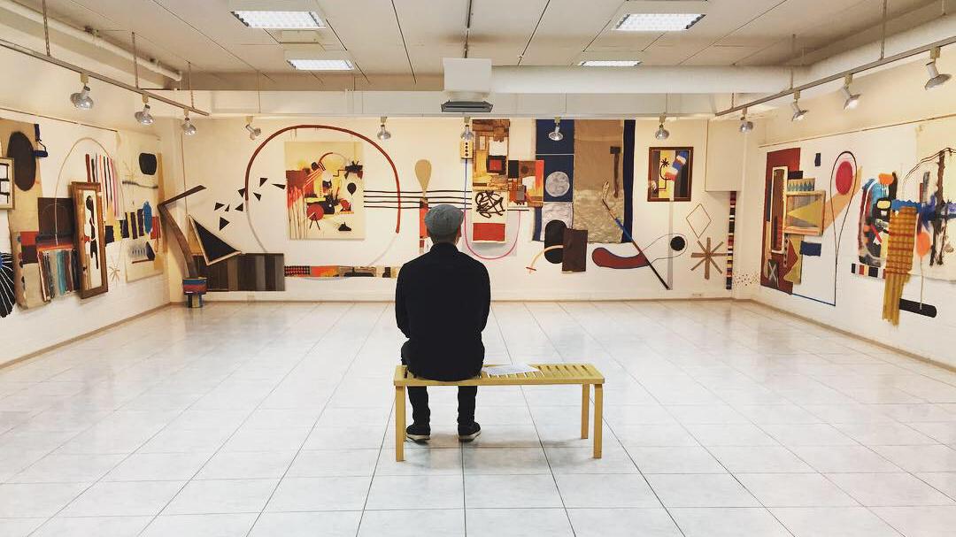 Mies istuu selin katsojaan penkillä vaaleassa, isossa salissa. Hän katselee seinille ripustettuja abstrakteja, värikkäitä taideteoksia. Kuvassa näkyy kolme seinää, jotka ovat aivan täynnä taideteoksia. Kuvan tunnelma on rauhallinen.