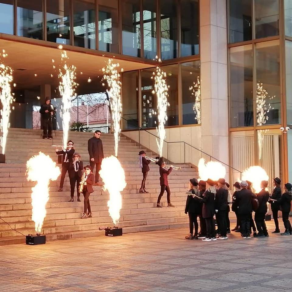 Kuva on otettu Kouvolan kaupungintalon portailla, kuvassa on Kouvolan apulaiskaupunginjohtaja Tuukka Forsell sekä pukuihin pukeutuneita nuoria soittajia tulisoihtujien keskellä.